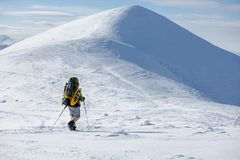 Backpacker man walking in winter mountains on sunny day Royalty Free Stock Images