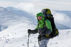 Backpacker man walking in winter mountains on sunny day Royalty Free Stock Photography