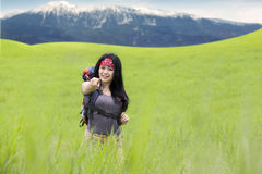 Backpacker on the meadow pointing at camera Royalty Free Stock Photography