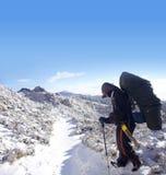 Backpacker met zware pakgang op de sneeuw royalty-vrije stock afbeelding