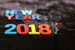 Backpacker miniatura que mira con el AÑO NUEVO 2018 del ` de la palabra, Foto de archivo