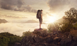 Backpacker on a mountain above the clouds Stock Images