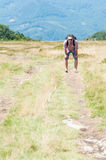 Backpacker on mountain footpath feeling tired Royalty Free Stock Photography