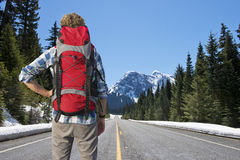 Backpacker on mountain road Stock Images