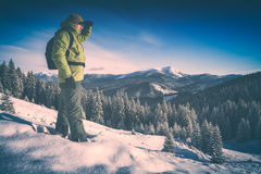 Backpacker on a mountain top. Instagram stylisation. Hiker standing on a hill covered with snow against winter mountain landscape and looking to the horizon Stock Images