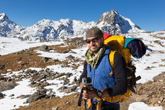 Backpacker mountaineer man portrait standing rest snow mountain. Royalty Free Stock Image