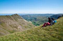 Backpacker in the Mountains. Backpacker having a rest and looking at the mountains. Striding Edge, Lake District, England Stock Photo