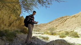 Backpacker in mountains with map stock video footage