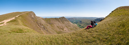 Backpacker in the Mountains - panorama. Backpacker having a rest and looking at the mountains. Striding Edge, Lake District, England Royalty Free Stock Photography