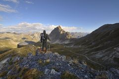 Backpacker observes the Alps Royalty Free Stock Photo