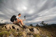 Backpacker op een rots die de afstand onderzoeken Royalty-vrije Stock Foto's