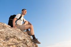 Backpacker op een rots die de afstand onderzoeken Stock Fotografie