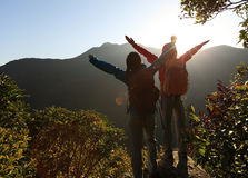 Backpacker open arms at mountain peak Stock Photos