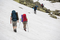 Backpacker passes snow field in rocky mountain in Altai mountain Royalty Free Stock Photography