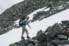 Backpacker passes snow field in rocky mountain in Altai mountain Royalty Free Stock Photo