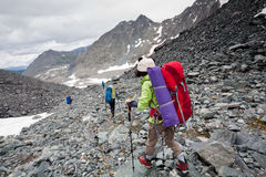 Backpacker passes snow field in rocky mountain in Altai mountain Stock Photo
