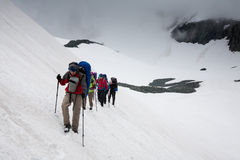 Backpacker passes snow field Royalty Free Stock Photos