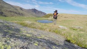 Backpacker and photographer hiking in the italian Alps stock footage