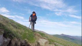 Backpacker and photographer hiking in the italian Alps stock video