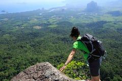Backpacker que mira abajo en el acantilado del pico de montaña Fotografía de archivo