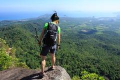 Backpacker que mira abajo en el acantilado del pico de montaña Imagen de archivo