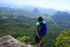backpacker que mira abajo en roca del top de la montaña Foto de archivo libre de regalías