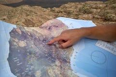 Backpacker que procura uma rota no mapa do turista Foto de Stock