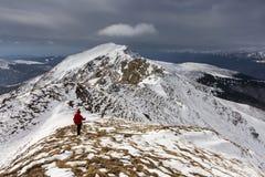 Backpacker que sube un invierno nevoso del canto de la montaña Foto de archivo