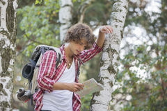 Backpacker reading map while leaning on tree trunk in forest Royalty Free Stock Images
