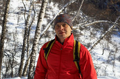 Backpacker in red in winter forest Royalty Free Stock Photos