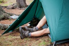 Backpacker is resting in green tent Royalty Free Stock Photo