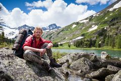 Backpacker is resting while hiking in mountains.  Royalty Free Stock Images