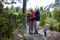 Backpacker is resting while hiking in mountains.  Royalty Free Stock Image