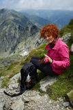 Backpacker resting on mountain trail Royalty Free Stock Photo