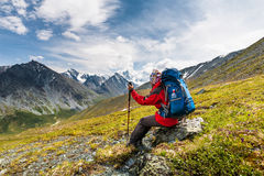 Backpacker rests in green highlands of Altai mountains. Russia Royalty Free Stock Photo