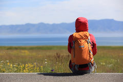 Backpacker sit on roadside taking a rest face the beautiful landscape Stock Photos