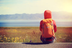 Backpacker sit on roadside taking a rest face the beautiful landscape Stock Photography