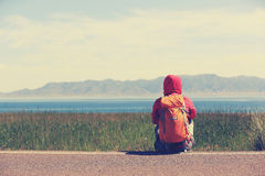 backpacker sit on roadside taking a rest face the beautiful landscape Royalty Free Stock Photo
