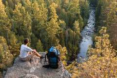 Backpacker sits on rock and look at a beautiful view Royalty Free Stock Photography