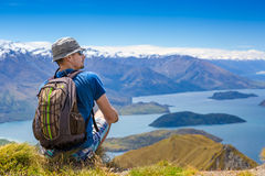 Backpacker sitting on a cliff and looking to a view Royalty Free Stock Images