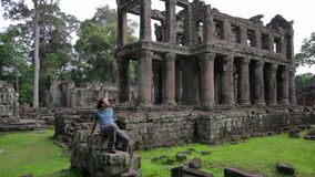 Backpacker sitting in preah khan temple, angkor, cambodia stock video