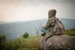 Backpacker sitting on the rock with beautiful nature. Background Royalty Free Stock Photography