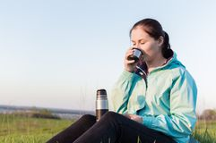 Travelling hiking backpacking sunset tourism. Backpacker sitting on the yoga mat outdoor and drinking tea from the vacuum bottle .Concept of the travelling Stock Photos
