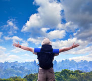 Backpacker spreads hands expressing happiness at tropical landsc Stock Photo