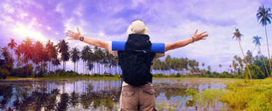 Backpacker spreads hands expressing happiness at tropical landsc Stock Images