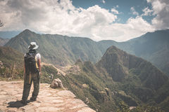 Backpacker standing in contemplation on the Inca Trail above Machu Picchu, the most visited travel destination in Peru. Rear view, Stock Photo