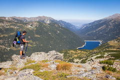 Backpacker standing mountain above lake. Royalty Free Stock Photos