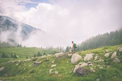 Backpacker standing on mountain footpath, toned Royalty Free Stock Photo