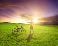 Backpacker standing next to bicycle with sunset background Royalty Free Stock Images