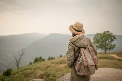 Backpacker standing on the rock with beautiful nature. Background Stock Photos
